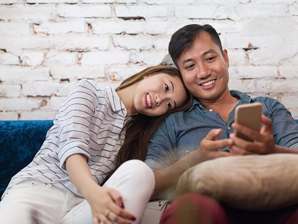 A young couple sitting on a sofa while looking at their phone