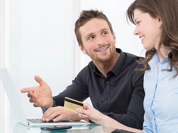 A young couple looking at their payment options while using their laptop
